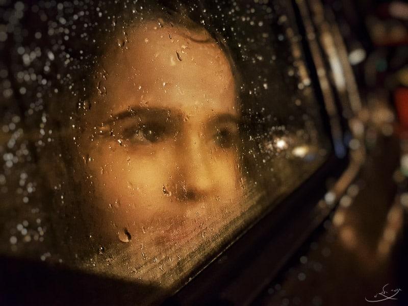 צילום במארטפון - ילדה מאחורי חלון רטוב של רכב